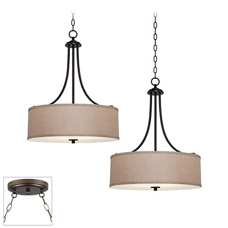 This stylish four-light orb chandelier is a transitional update to a classic open, intersecting sphere design. In buckeye bronze finish, crisp tapered shades cover the lights on curved arms, with a clear crystal center column and accents.